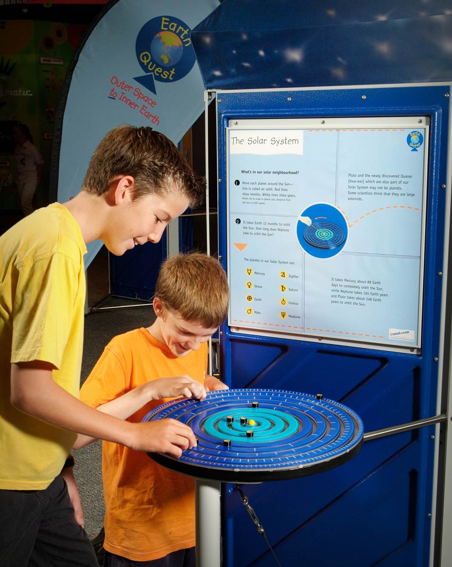 Two boys are playing with a blue disc with black markers that represents the solar system. In the background is a blue and white information panel.