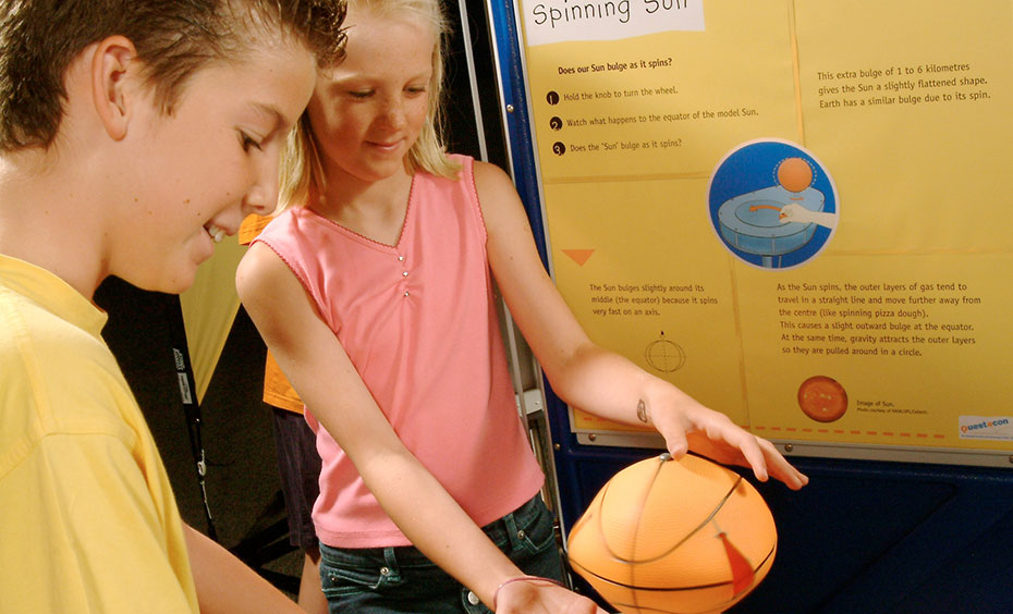 A boy and girl standing next to a small basket ball on top. In the background are yellow and blue information panels.