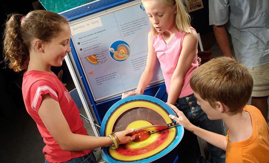 Two girls and a boy looking at a red, yellow and blue cross section of the earth showing the different layers. Behind them is a blue information panel.