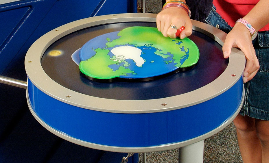 A blue and beige round table has a flat earth picture on top with a red handle, which has a child's hand moving it.