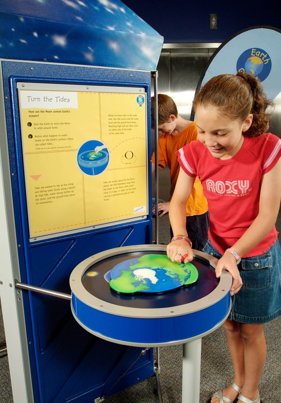 A young girl is standing next to a yellow and blue table and exhibition panel. She is winding a red handle on the surface of the table which in turn is attached to a flat blue, white and green earth picture.