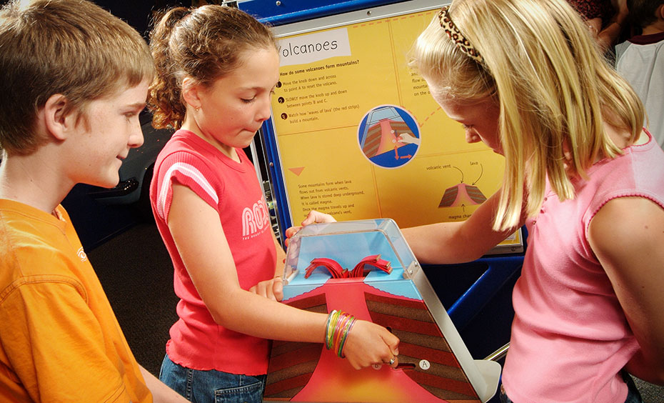 A boy and two girls are standing around a exhibit that has a yellow and blue information panel at the back. In the centre of the group is a model volcano.