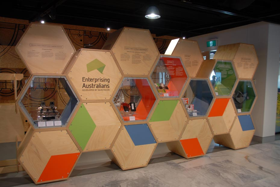 A timber and glass display case shaped as many interlocking hexagional prisims. The case is titled Enterprising Australians, developed by Questacon.