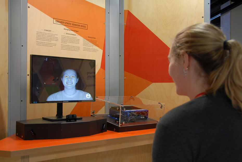 a woman sitting at a table and seeing her own face displayed on a monitor on the table. Her face, displayed by the monitor, has lines drawn on it.