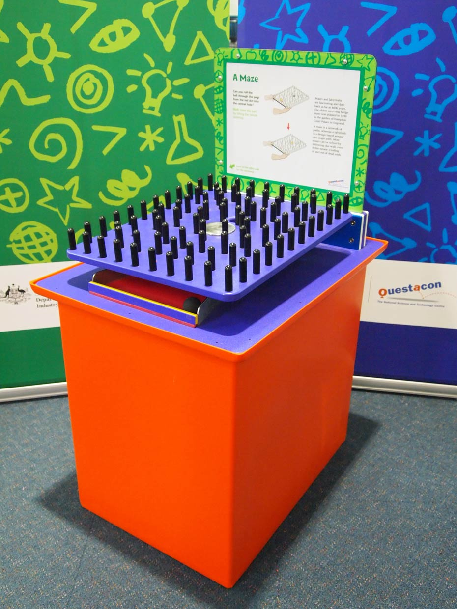 An orange and purple exhibit table with a green and white information panel at the back, and a purple square plate on top of the table that has black pegs facing upwards.