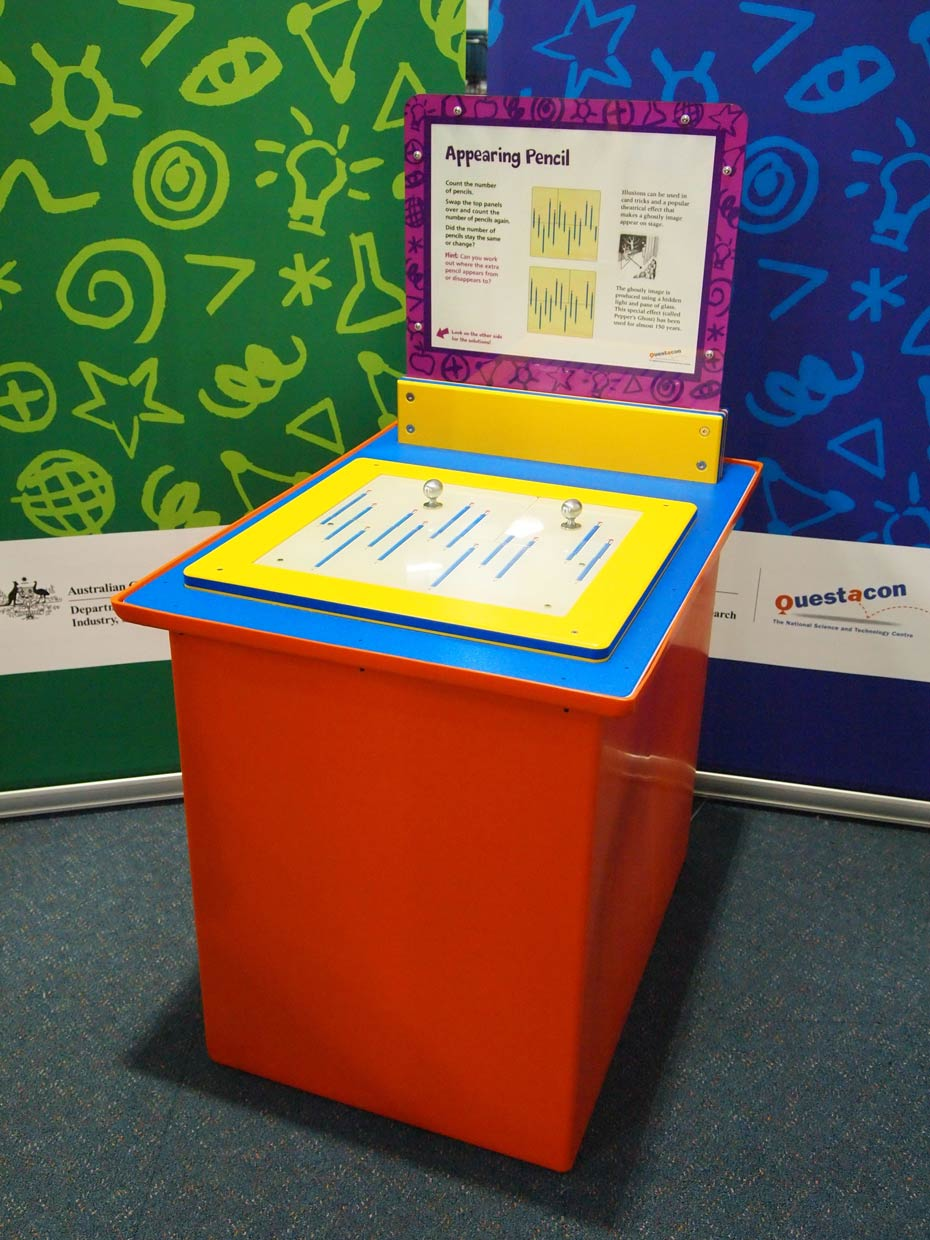 A red and blue and yellow exhibit table with a purple and white information panel on top, sits in front of green and blue walls. On the table there are two brushed metal knobs with pictures of muliple blue pencils.