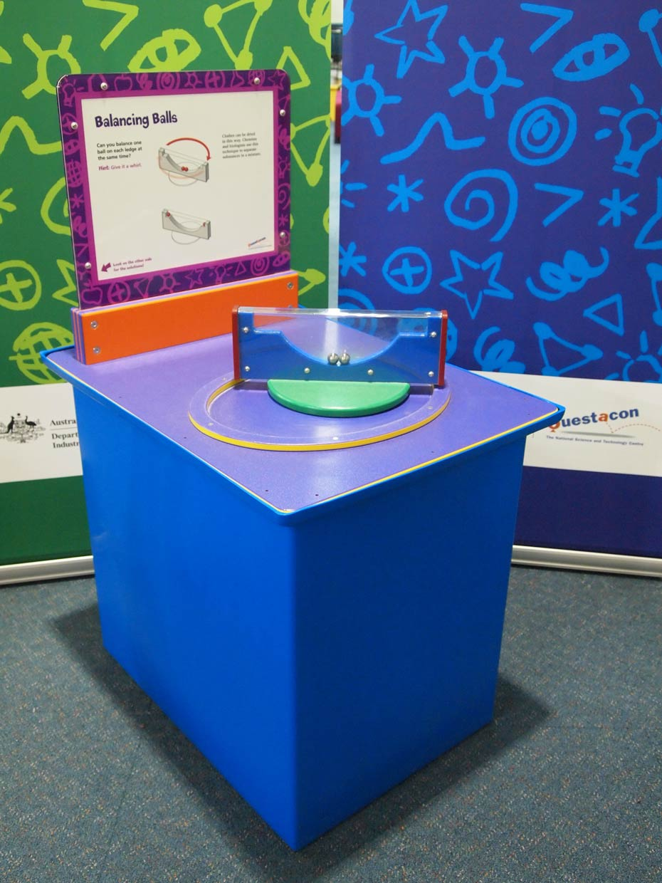 A blue and purple exhibit table with an orange, purple, and white information panel on top of it, sits in front of two green and blue walls. On the table is a rectangular blue and clear perspex shape sitting on edge that has two silver balls inside.