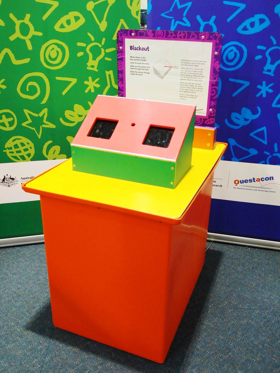 A red and yellow exhibit table with an orange, white and purple information panel at the back, sits in front of two green and blue walls. On the table is a rectangular box with a sloped face and two square black areas.