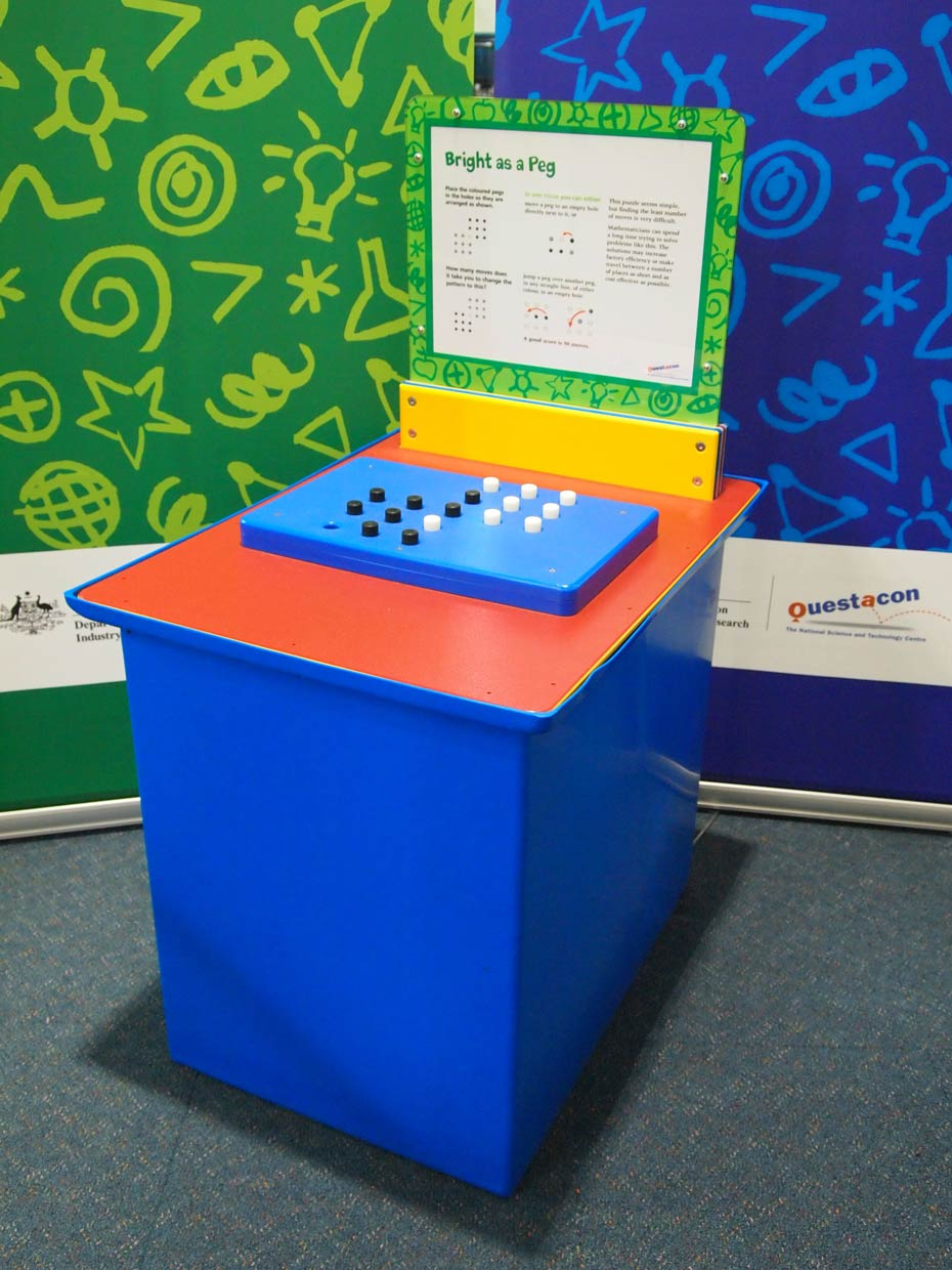 a blue and orange exhibit table with a yellow, white and green information panel, sits in front of two blue and green walls. On the table lays a blue rectangle shape with black and white pegs sitting on top.