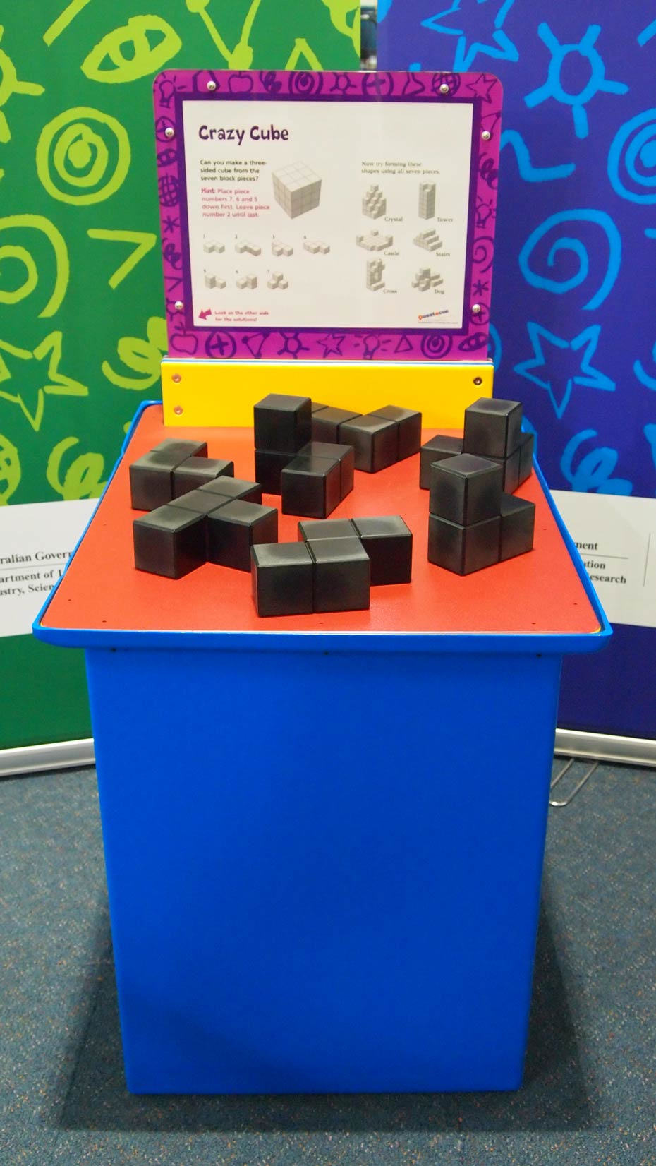 A blue and orange exhibit table with a yellow, white and purple information panel on top, sits in front of two green and blue walls. On top of the table are an array of small black cubes joined together in different shapes.