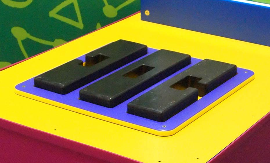 Three black shapes sit flat on a blue and yellow flat surface.
