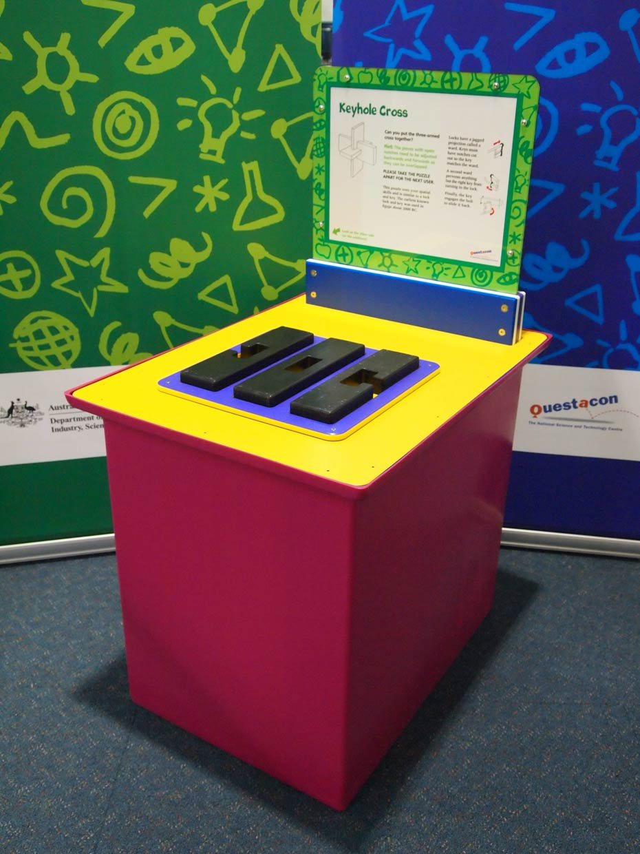 A red and yellow exhibit table with a blue, green and white information panel at the back, sit in front of two green and blue walls. On the table is a flat blue shape, with three black shapes on top.