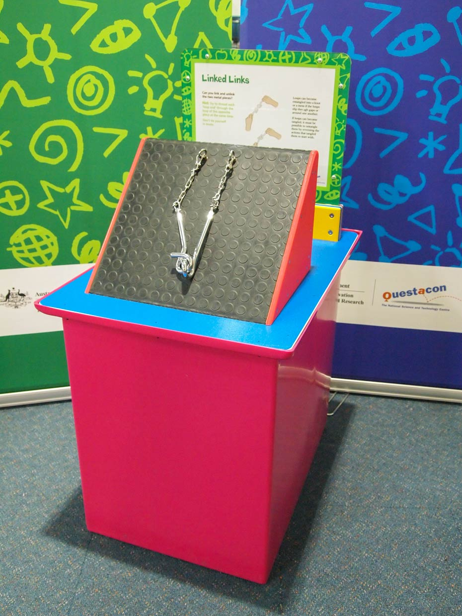 A red and blue exhibit table, with a yellow, green and white informatiion panel on top, sits in front of two green and blue walls. On thed by chains to a black and red triangular prism. e table sits two stainless steel hoops attach