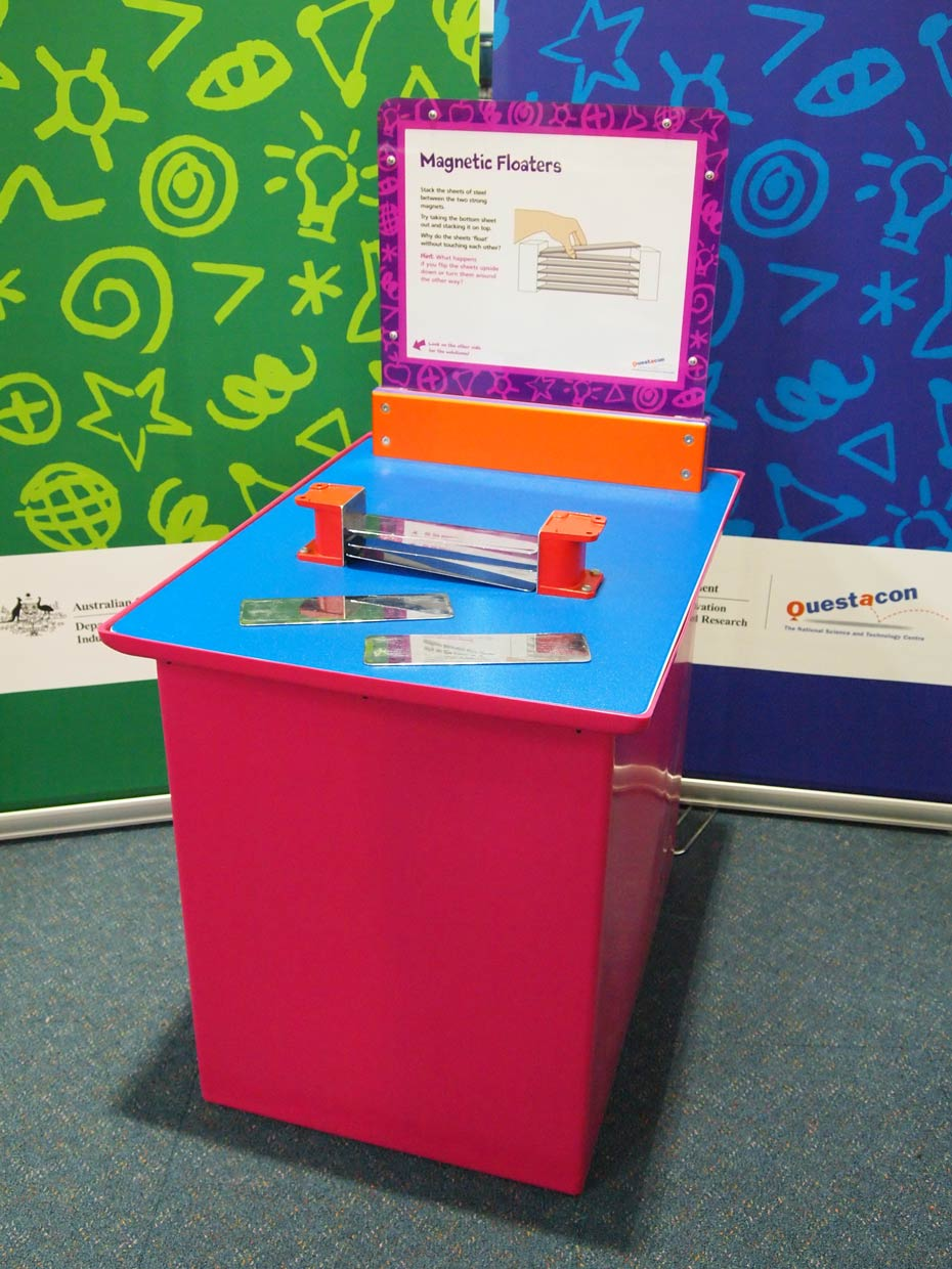 A red and blue exhibit table with an orange, white and purple information panel on top, sits in front of a green and a blue wall. On the table top sits two orange end pieces that have flat chrome metal pieces suspended between them.
