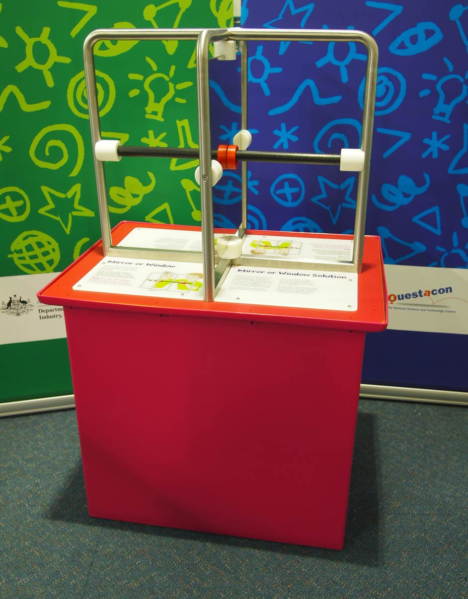 A red exhiibit table with white infomation panels on the table top, sits in front of a green and a blue wall. On the table sits two steel frames at right angles to one another with mirrors and air gaps inbetween them.
