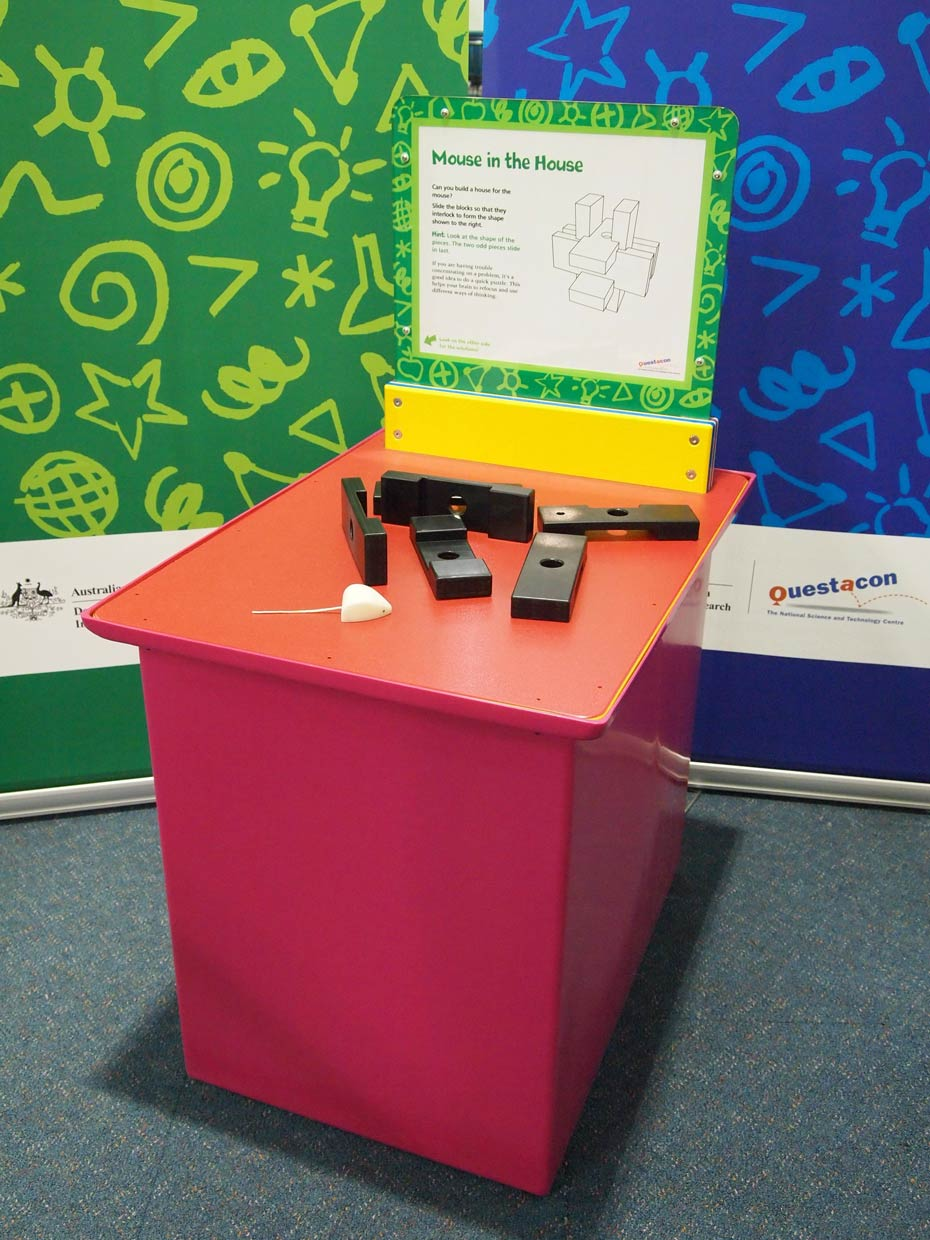 A red and orange exhibit table, with a green, white and yellow information panel on top, sits in front of a green and a blue wall. On top of the table are five black blocks, and a toy white mouse.