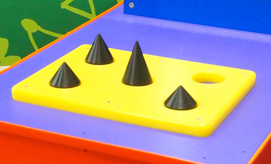 A yellow flat board, with four black cones pointing upwards.