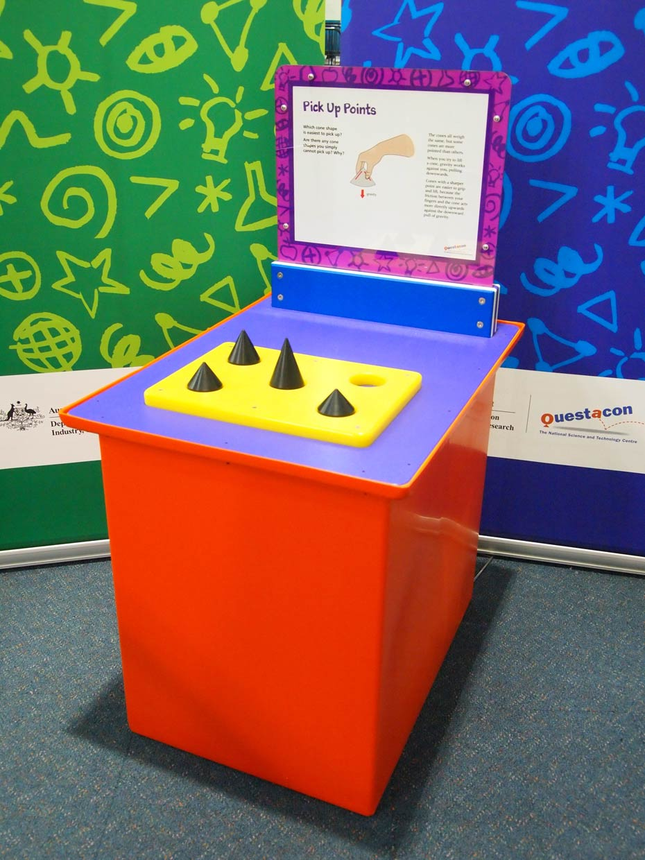 A red and purple exhibit table, with a blue, white and purple information panel on top, sits in front of a green and a blue wall. On the table is a yellow flat board, with four black cones pointing upwards.