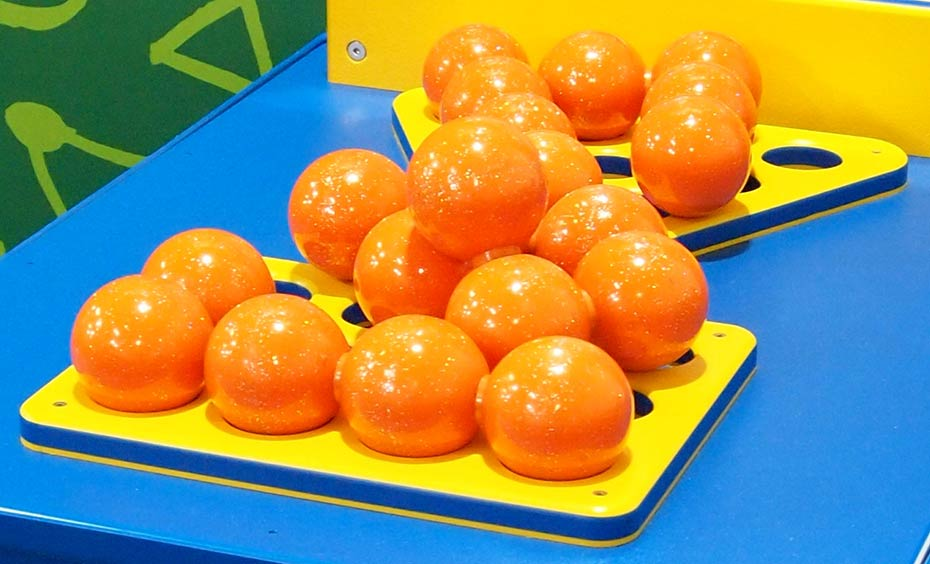 On a blue surface are a triangle shaped and a rectangle shaped yellow flat base, on which sits piles of orange balls.