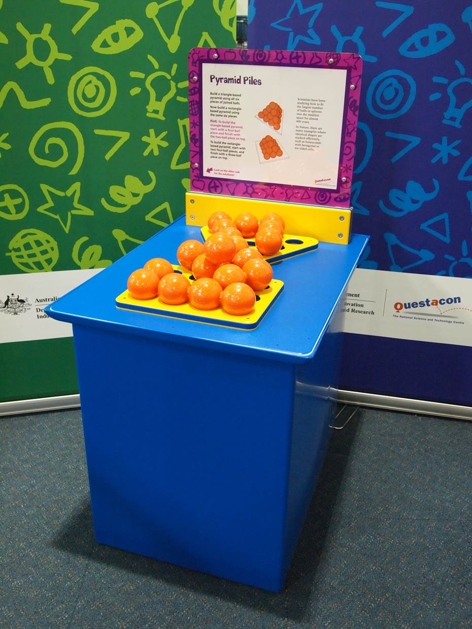 A blue exhibit table, with a yellow, white and purple information panel on top, sits in front of a green and a blue wall. On the table are a triangle shaped and a rectangle shaped yellow flat base, on which sits piles of orange balls.