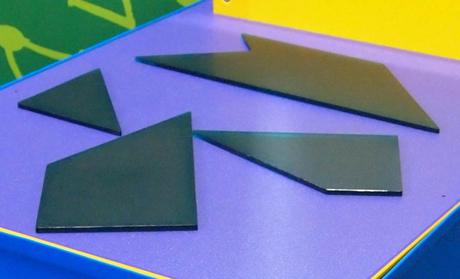 Four flat black shapes sit on a purple surface.