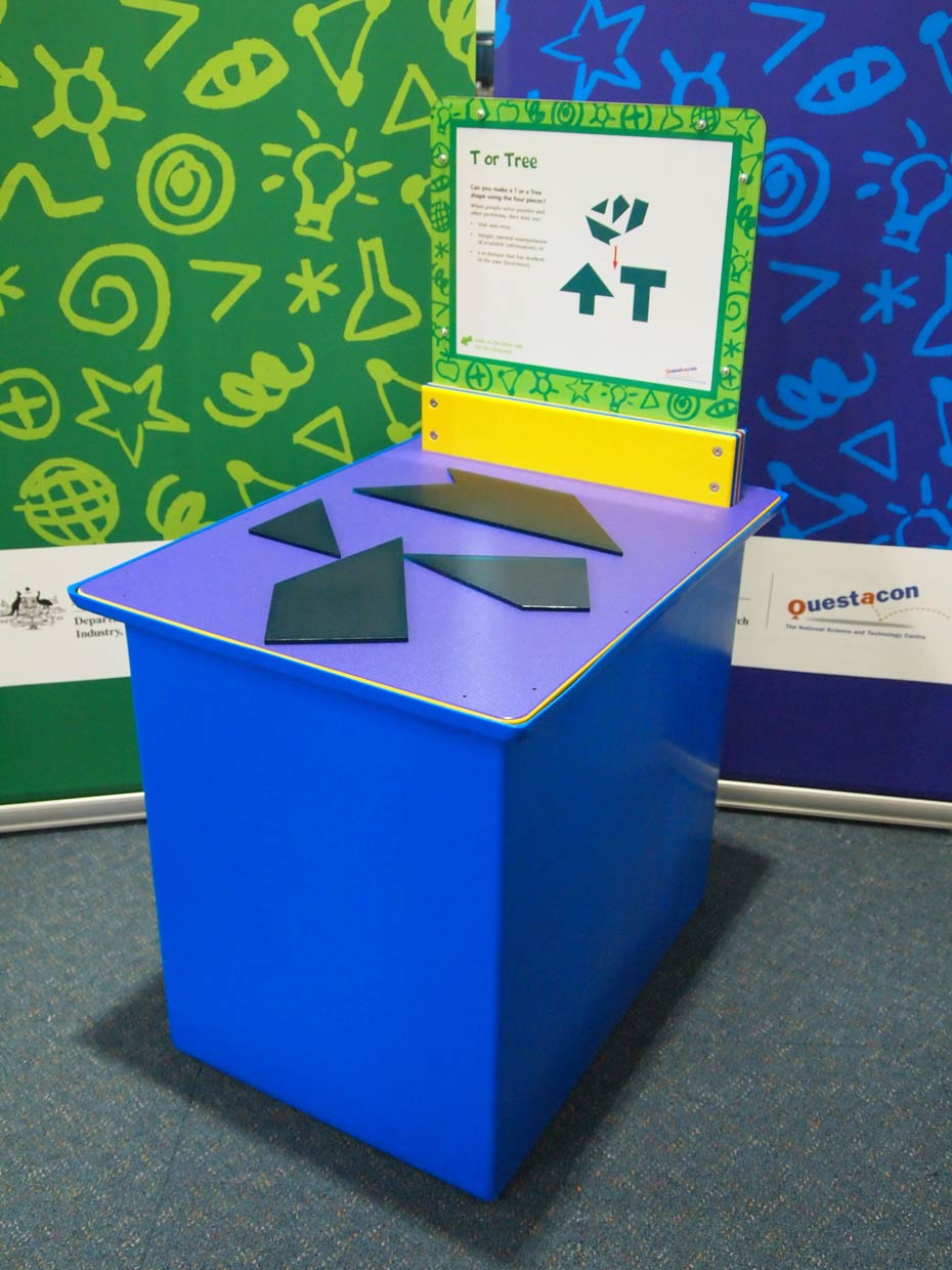 A blue and purple exhibit table, with a yellow, green and white information panel on top, sits in front of a green wall and a blue wall. On top of the table site four black flat shapes.
