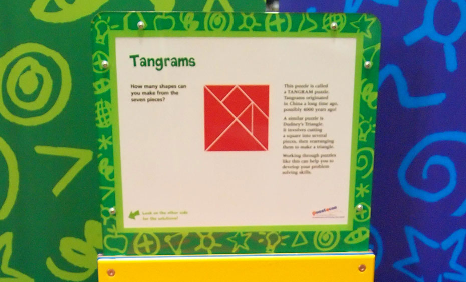 A yellow, green, red and white information panel with the title 'Tangrams'. In the centre of the panel is a red square that is made up of different small shapes.