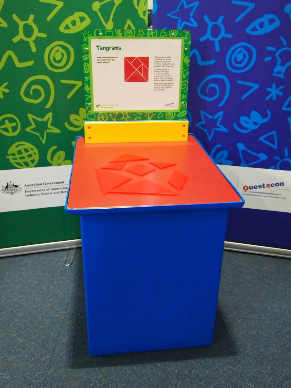 A blue and orange exhibit table, with a yellow, green and white information panel on top, and a green and a blue wall behind. On top of the table are a range of differnt flat orange shapes.