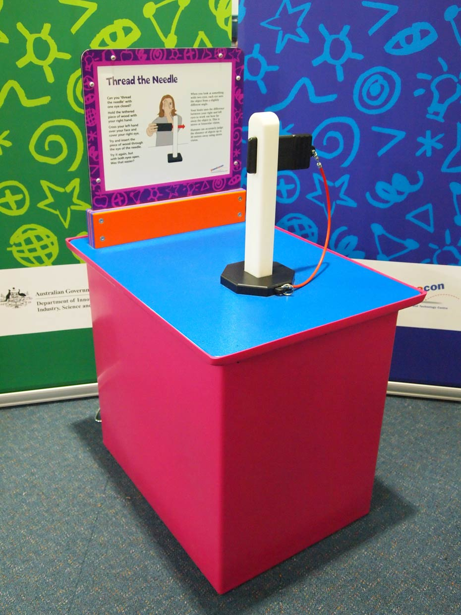 A red and blue exhibit table, with an orange, purple and white information panel at the back, sits in front of a green and a blue wall. On the table is a white vertical post with a slot in the top, that has a black rectangle inserted into the slot.