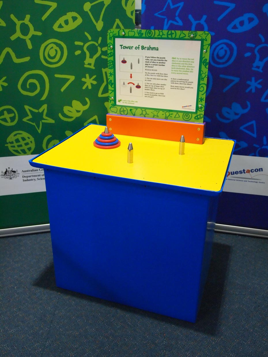 A blue and yellow exhibit table, with a green, white and orange information panel on top, sitting in front of a green and a blue wall. On the yellow tabel top are three chrome pegs, of which one has five red and blue discs that are threaded onto the peg, and arranged from largest to smallest.
