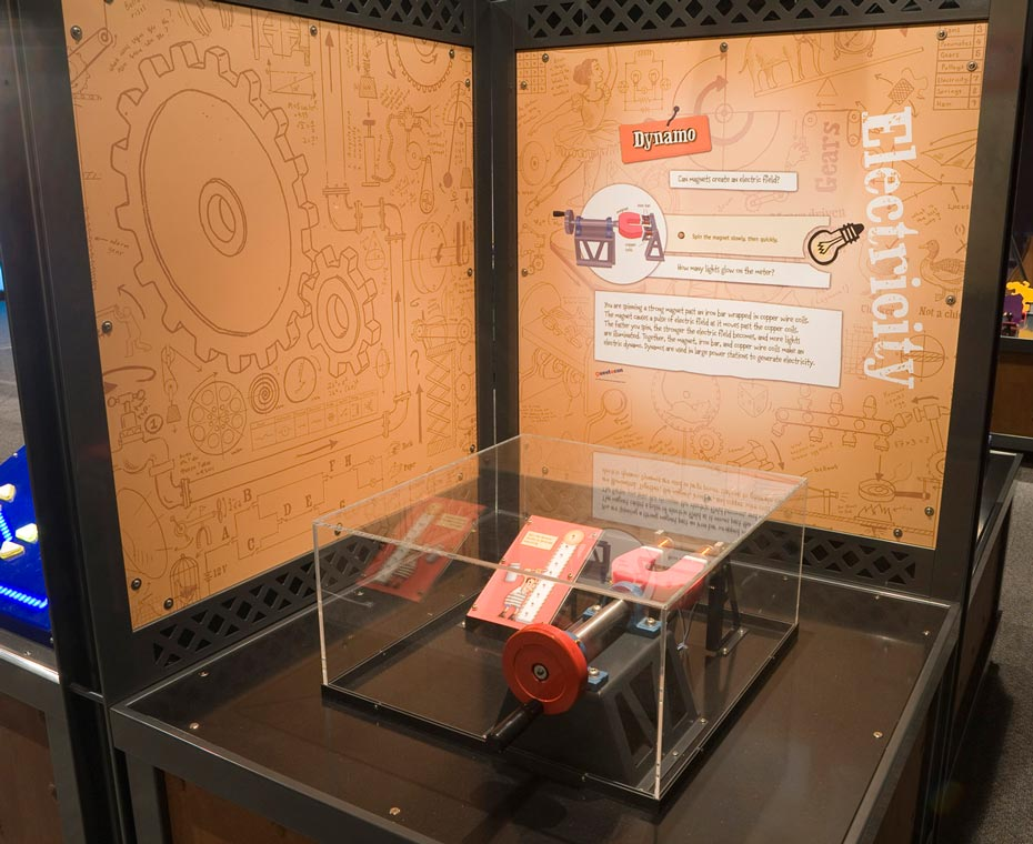 A red mechanical dynamo device enclosed in clear pespex sits on a black bench, that is surrounded on two sides by brown and white information panels.