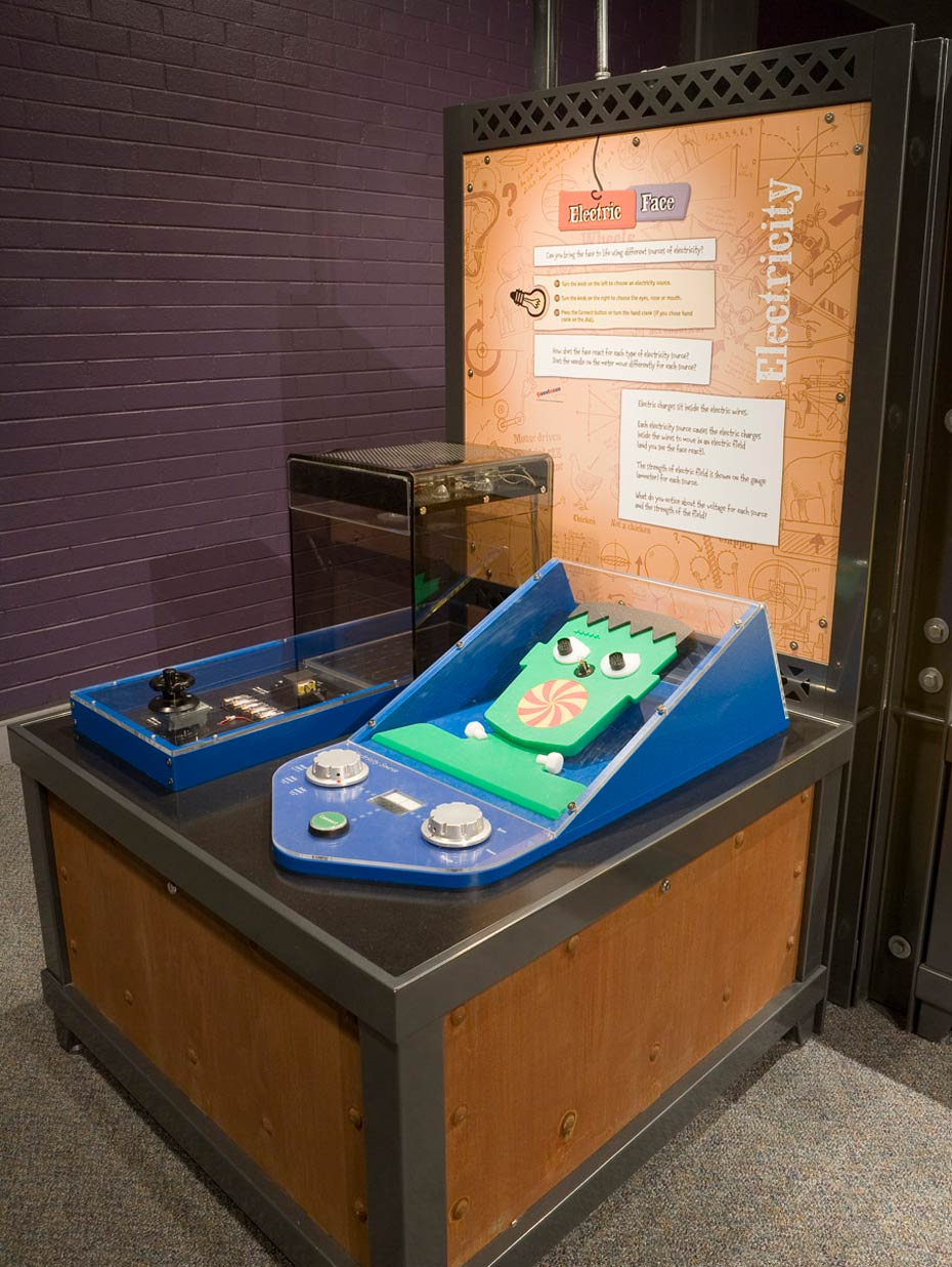 A timber and steel exhibit table with matching information panel at the back. On the table are two blue interactive objects, of which one has a green cut out face.