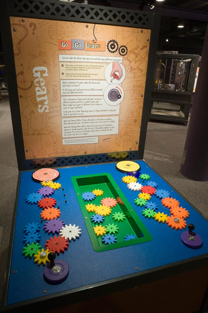 A blue and black table with a brown and white information panel at the back. On the table top, sits multiple different coloured and sized gears, interlinked and sitting in a green tub.