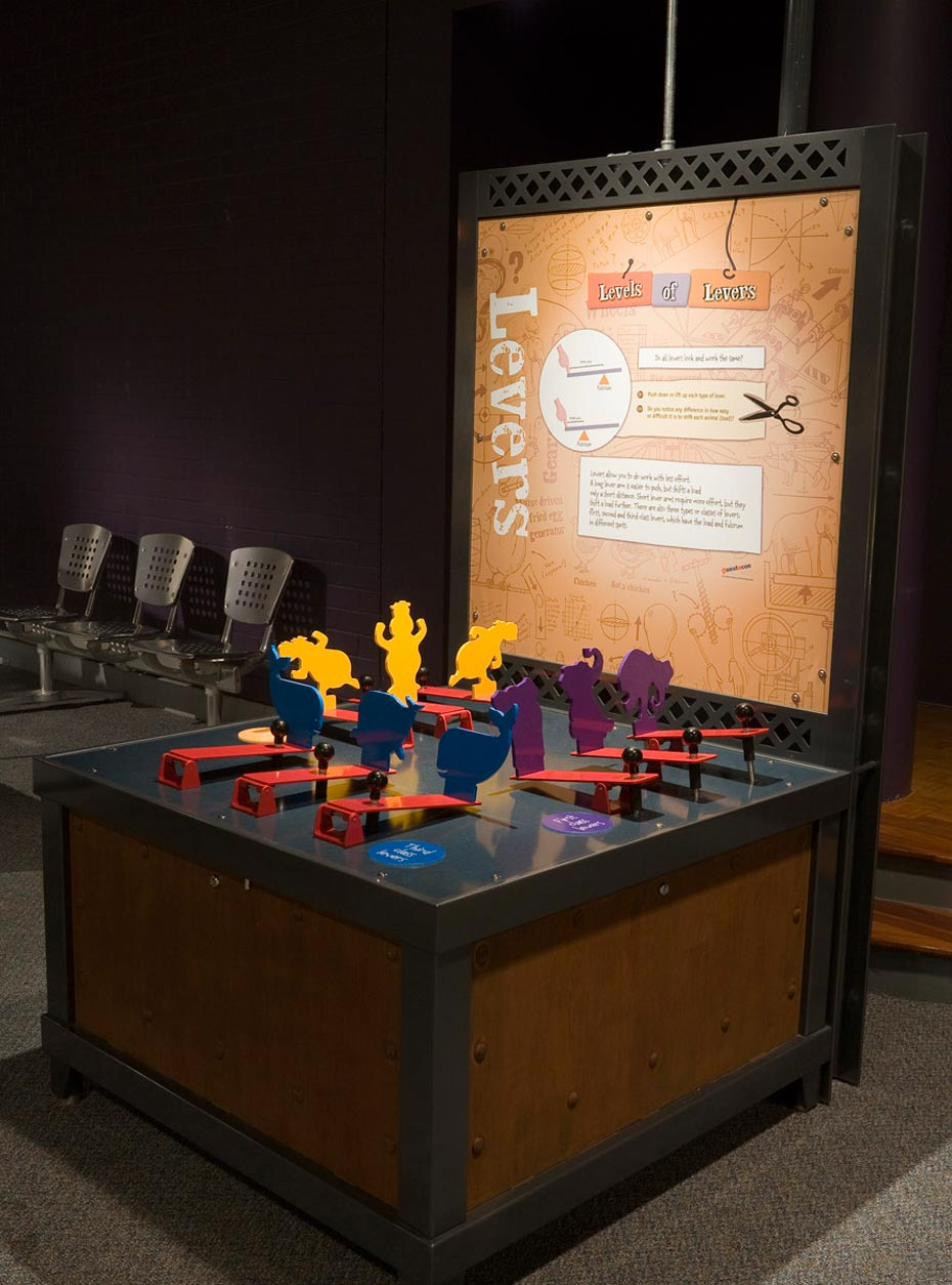 A timber and black exhibit table, with a brown and white information panel at the back. On the table top sits three rows of red levers with yellow, blue and purple cut out animals shapes.