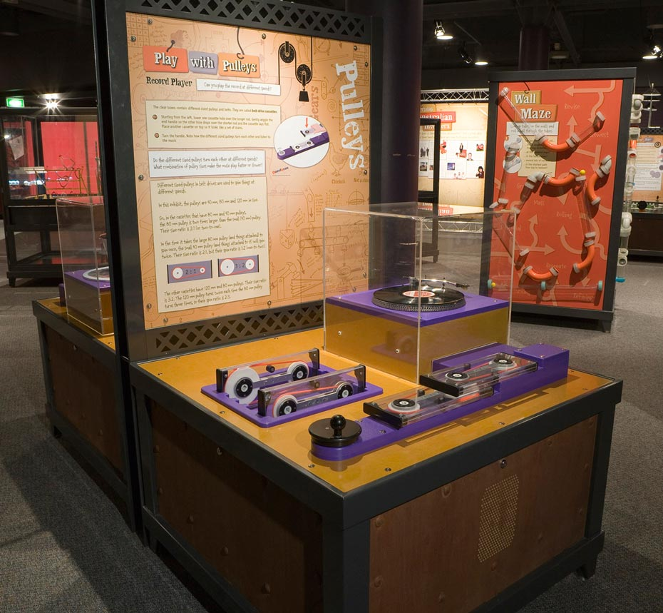 A timber, black steel and yellow exhibit table with a matching vertical information panel at the back. On the table top sits a record player in a perspex box surrounded by purple and black gears contained in rectangular perspex boxes.
