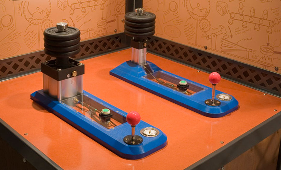A timber, black and orange exhibit table with two information panels at the rear in the same colour scheme. On the table top sits two piston devices with blue bases and a series of weights at one end. Thre is a red joystick and pressure guage at the other end.