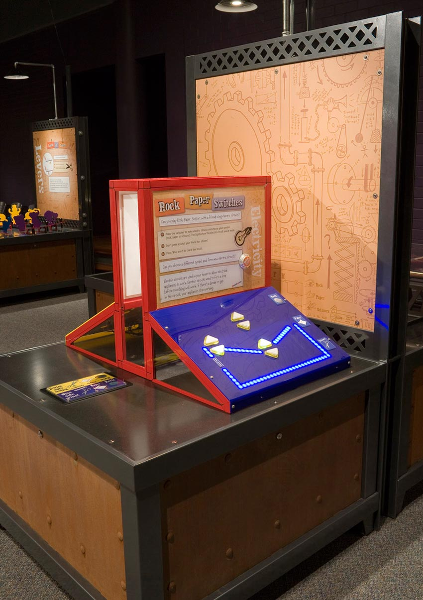A timber and black exhibit table with a red, brown, white and blue exhibit sitting on the table top. The exhibit has a sloping blue face with arrow buttons on it, and a vertical information panel at the back.