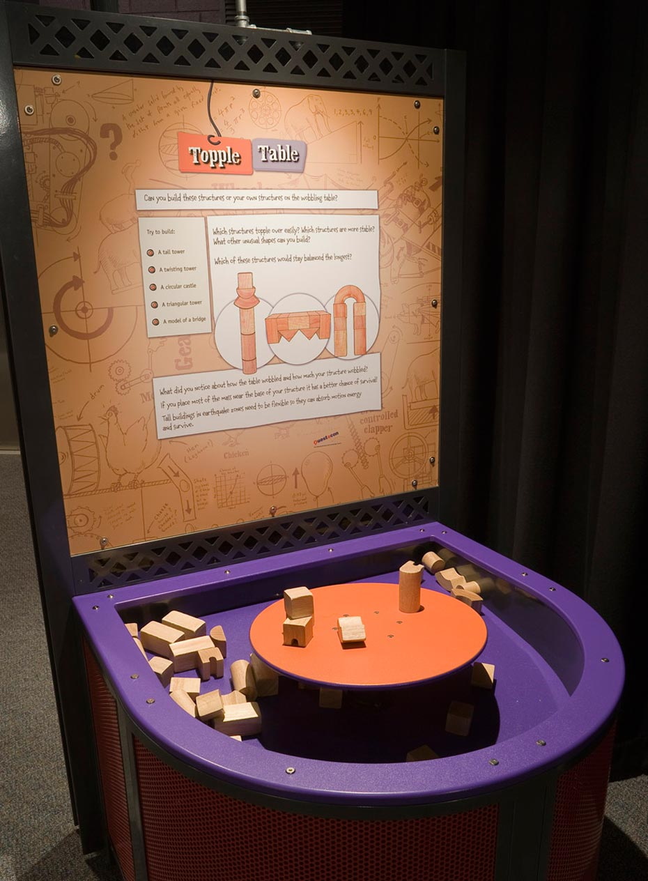 A large purple tray containing wooden building blocks, has a raised orange round platform in the centre of it. At the back of the purple tray is a brown and white information panel.