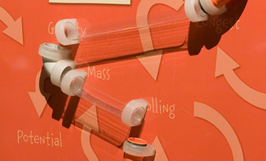 An orange vertical surface, with clear plastic piping attached. the words 'potential', 'mass', and 'longest' are displayed along with arrows pointing in every direction.