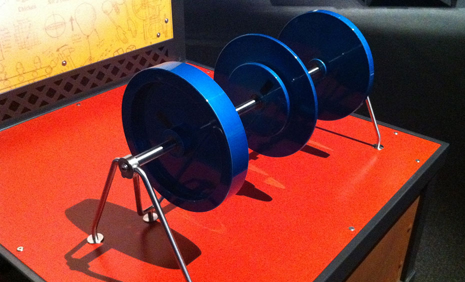 A series of three blue wheels of different thicknesses sitting on a red table.