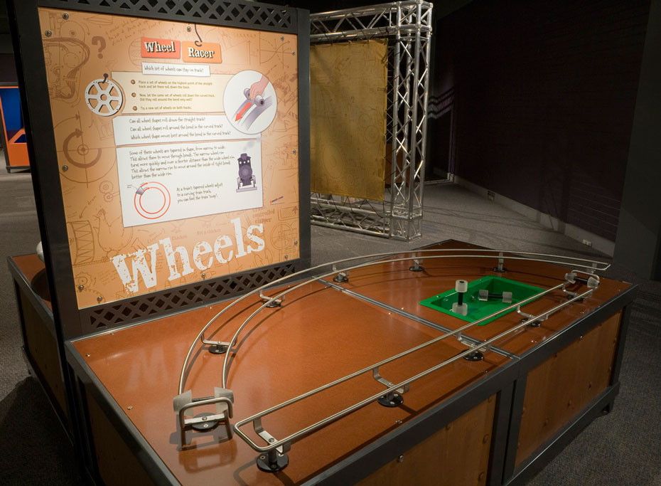 A brown and black exhibit table with matching information panel at the back. On the table is a D shaped rail with wheels sitting on the track.