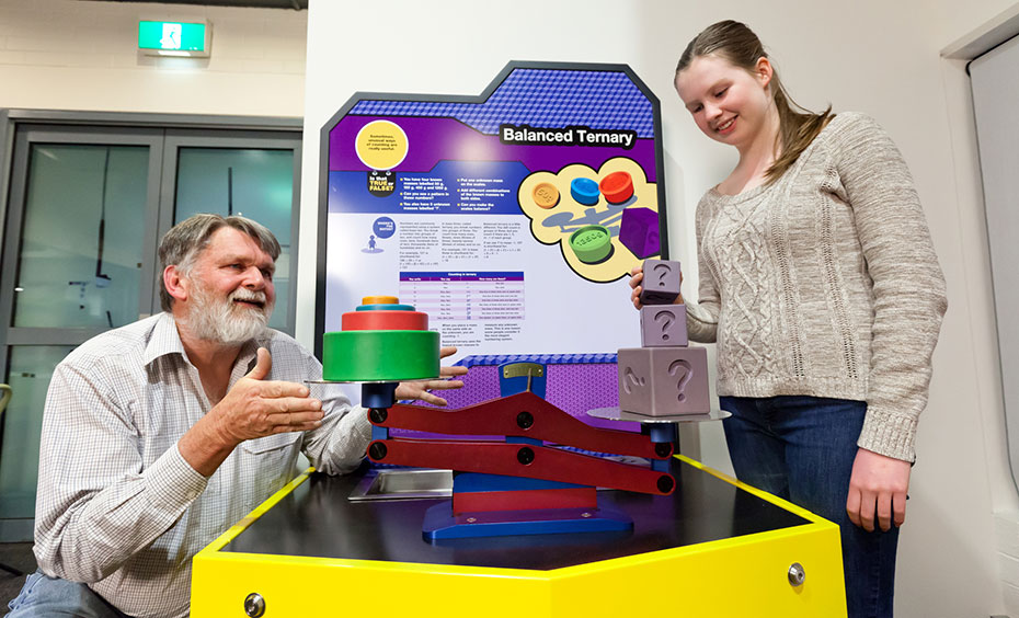 A father and daughter are standing next to a brightly coloured exhibit table that features a red and blue scale, and has both different sized grey blocks and coloured round discs balanced upon it.
