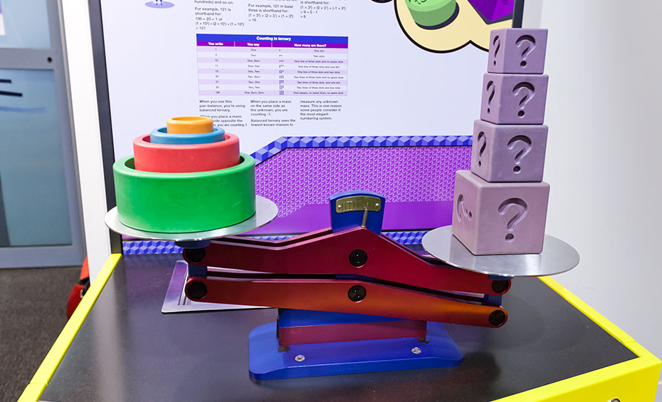A red and blue scale with 4 purple blocks on one side and coloured weights on the other.