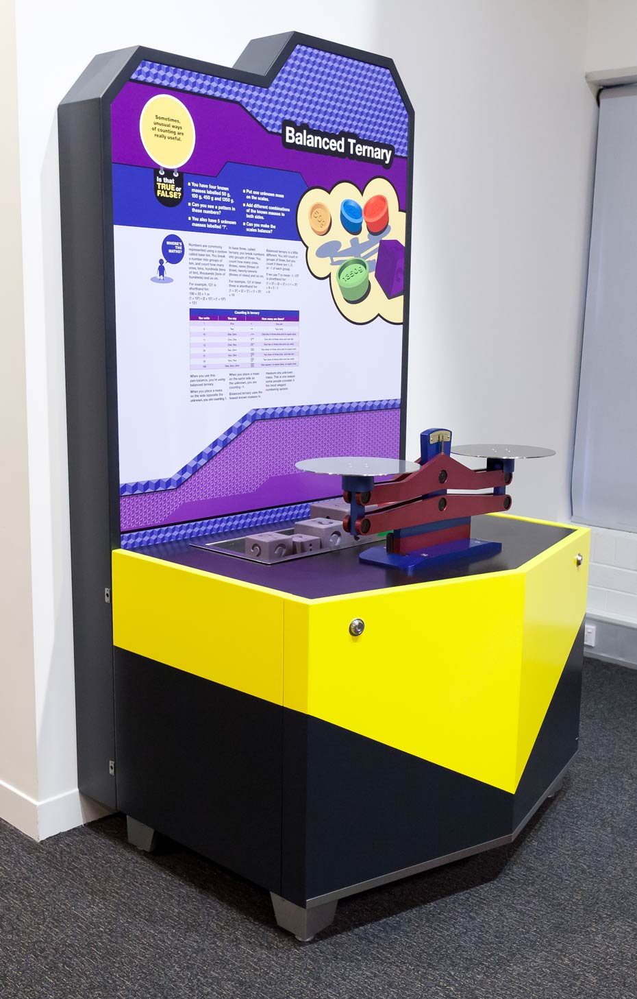 A black, yellow, white and purple exhibit sitting in a white room. On the exhibit table sits a blue and red scale.