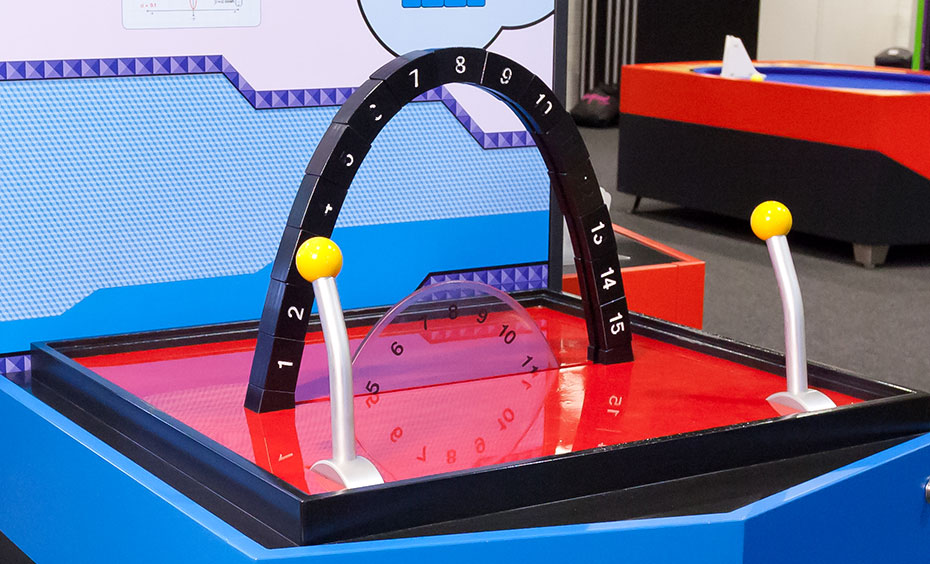 A black, blue and red exhibit table with an information panel at the back. On the table top are two joysticks and a series of black blocks in the shape of an arch.