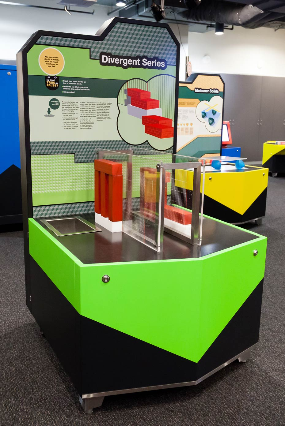 A black, green and grey exhibit table with vertical information panel and a series of red and white blocks on the table surface.
