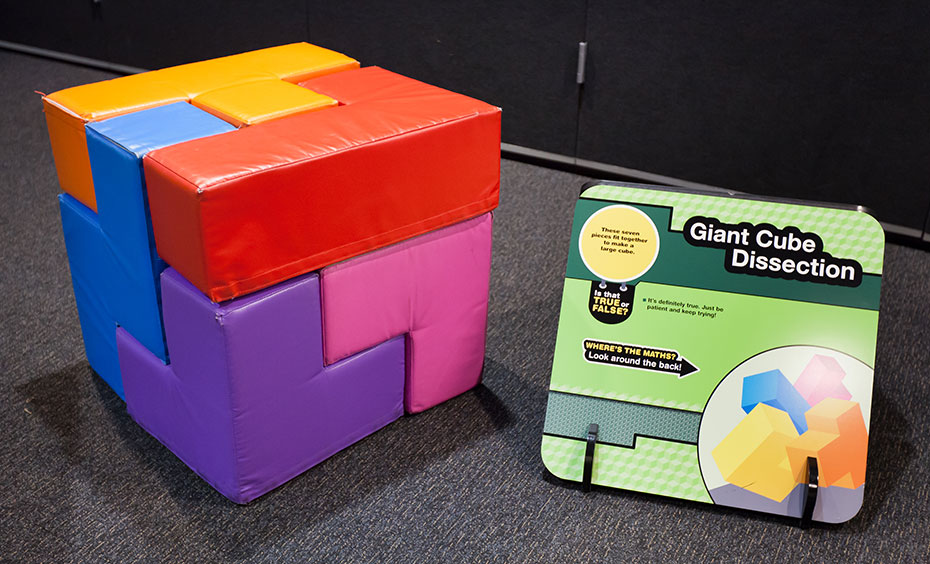 A colourful soft cube shape that has interlocking pieces, sits beside a green information panel.