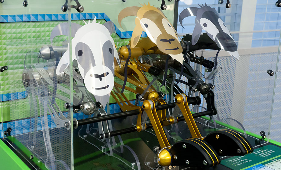 A white, gold and grey coloured mechanical goats sitting on a green and blue exhibit table.