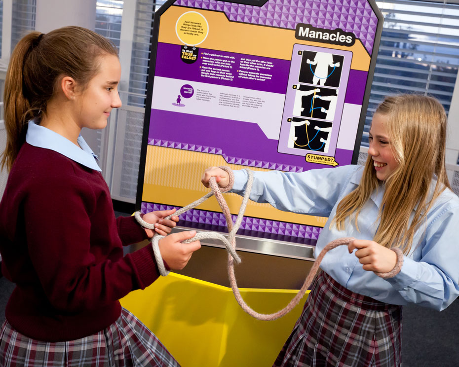 Two school girls standing in front of an exhibition table. They are two ropes intertwined between them.