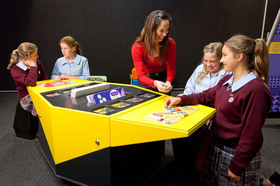 A wowan and four school girls are sitting next to a yellow and black table that has an assortment of maths puzzles on top.